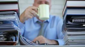 Biznesmen praca w księgowości archiwum używa wiszącą ozdobę i pije kawę zbiory