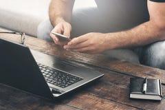 Biznesmen pracuje laptop i smartphone na kanapie w domu Obraz Stock