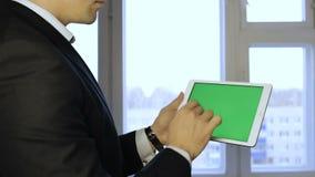 Biznesmen pracuje na holograficznym interfejsie Mężczyzna w kurtce, macanie, projekta ekran, białe ikony na pastylce zdjęcie wideo