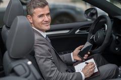 Biznesmen pracuje na jego samochodzie Fotografia Royalty Free