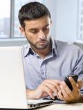 Biznesmen pracuje na komputerowym laptopie używać telefon komórkowego przy biurowym biurkiem przed drapacza chmur okno zdjęcia stock