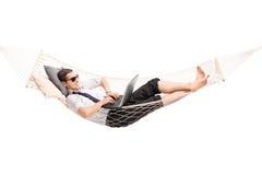 Biznesmen pracuje na laptopie i lying on the beach w hamaku zdjęcia royalty free