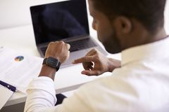 Biznesmen Pracuje Na laptopie Przy biurkiem W Nowożytnych Biurowych Sprawdza dane Na smart watch fotografia stock