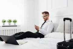 Biznesmen pracuje od pokoju hotelowego z jego telefonem komórkowym Fotografia Royalty Free