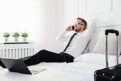 Biznesmen pracuje od pokoju hotelowego z jego telefonem komórkowym Zdjęcia Royalty Free