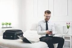 Biznesmen pracuje od pokoju hotelowego z jego telefonem komórkowym Fotografia Stock