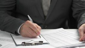 Biznesmen pracuje przy biura i cyrklowania finanse, czyta raporty i pisze biznesowy pieniężnej księgowości pojęcie zbiory