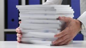 Biznesmen pracuje przy biurem i broguje książki zbiory