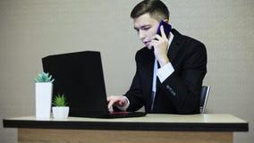 Biznesmen pracuje przy biurem na laptopie, pisać na maszynie i mówi telefonem komórkowym zbiory wideo