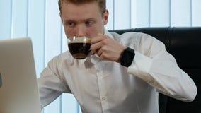 Biznesmen pracuje przy biurowym biurkiem z jego laptopem i pije kawę otaczającą mnóstwo papierkową robotą i pieniężną zbiory