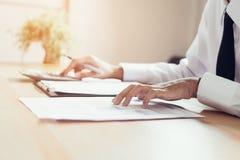 Biznesmen pracuje przy jego biurem z dokumentami i sprawdza dokładność informacja obrazy stock