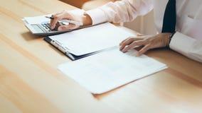 Biznesmen pracuje przy jego biurem z dokumentami i sprawdza dokładność informacja obraz royalty free
