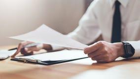 Biznesmen pracuje przy jego biurem z dokumentami i sprawdza dokładność informacja fotografia royalty free