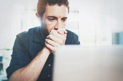 Biznesmen pracuje przy nowożytnym loft biurem Zadumany mężczyzna obsiadanie i używać współczesnego laptop zamazujący tło Zdjęcia Royalty Free