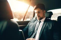 Biznesmen pracuje wśrodku samochodu podczas gdy podróżujący Fotografia Stock