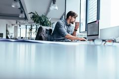 Biznesmen pracuje w biurze z telefonem Obraz Royalty Free