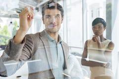 Biznesmen pracuje z bizneswomanem i pisze na przejrzystej desce zdjęcia royalty free