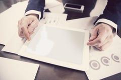 Biznesmen pracuje z cyfrową pastylką przy biurem fotografia royalty free
