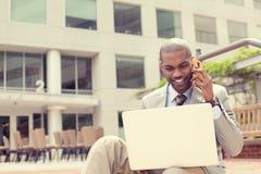 Biznesmen pracuje z laptopem outdoors opowiada na telefonie komórkowym Zdjęcie Stock