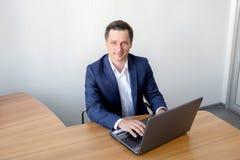 Biznesmen pracuje z laptopem w biurze jest przyglądający kamera Obraz Royalty Free