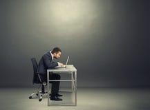 Biznesmen pracuje z laptopem w ciemnym pokoju obrazy stock