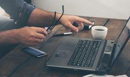 Biznesmen pracuje z laptopu biurem w domu na drewnianym stole Zdjęcia Stock