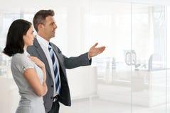 Biznesmen przedstawia bizneswoman przy biurem Zdjęcia Royalty Free
