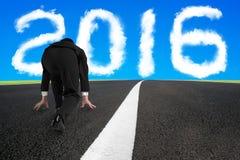 Biznesmen przygotowywający bieg na asfaltowej drodze z 2016 chmurą Obrazy Stock