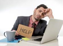 Biznesmen pyta dla pomocy mienia kartonu w kostiumu i krawata obsiadaniu przy biurowym biurkiem pracuje na komputerowym laptopie  Obrazy Stock