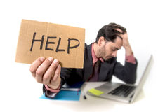 Biznesmen pyta dla pomocy mienia kartonu w kostiumu i krawata obsiadaniu przy biurowym biurkiem pracuje na komputerowym laptopie  Fotografia Stock