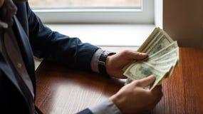 Biznesmen ręka chwyta pieniądze, dolara amerykańskiego USD rachunki Mężczyzna w kostiumu Drewniany tło fotografia stock