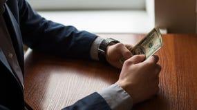 Biznesmen ręka chwyta pieniądze, dolara amerykańskiego USD rachunki Mężczyzna w kostiumu Drewniany tło obraz royalty free