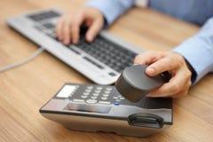Biznesmen ręka podnosi up telefonicznego odbiorcę na biznesowym workp Zdjęcie Royalty Free