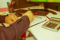 Biznesmen ręka używać pióro dla pisać dane informaci na papierkowej roboty pojęciu Biznesmen robi niektóre papierkowej robocie uż Obraz Royalty Free