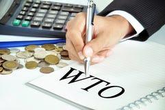 Biznesmen ręka z piórem wskazuje WTO lub światowa organizacja handlu znak () Zdjęcia Stock