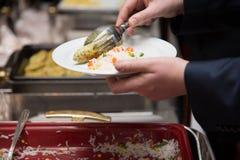 Biznesmen ręki bierze jedzenie w bufet linii salowej w bakłaszce obraz stock