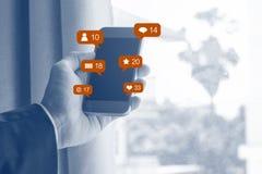 Biznesmen ręki mienia mobilny mądrze telefon z ogólnospołecznymi środkami i ogólnospołeczną sieci powiadomienia ikoną, zdjęcie stock