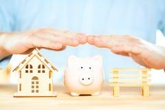 Biznesmen ręki nad prosiątko bank, domu model i ławka, Hipoteczna planu, asekuracyjnej i mieszkaniowej podatku oszczędzania strat fotografia royalty free