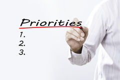Biznesmen ręki writing priorytety z czerwonym markierem na transpare fotografia stock