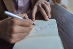 Biznesmen ręki z pióra writing notatnikiem na drewnianym biurko stołu zakończeniu up Biznesowego planowania pojęcie Zdjęcie Stock