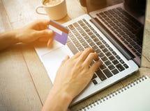 Biznesmen ręka trzyma kredytowej karty i use laptopu rocznika tonuje Zdjęcie Royalty Free