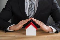 Biznesmen ręki chronienia domu model Obrazy Stock