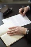 Biznesmen ręki z pióra writing notatnikiem na biurowego biurka stole Obrazy Stock