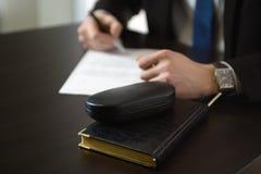 Biznesmen ręki z pióra writing notatnikiem na biurowego biurka stole Zdjęcia Stock