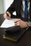 Biznesmen ręki z pióra writing notatnikiem na biurowego biurka stole Obraz Stock