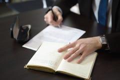 Biznesmen ręki z pióra writing notatnikiem na biurowego biurka stole Zdjęcia Royalty Free