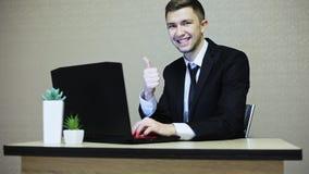 Biznesmen robi aprobatom podczas gdy pracujący na laptopie zbiory