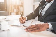 Biznesmen robi notatkom w papierach siedzi przy biurkiem obrazy royalty free