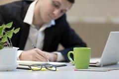 Biznesmen robi ręk notatkom przy Biurowym pracującym miejscem obraz royalty free