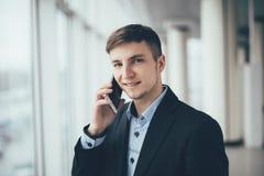 Biznesmen rozmowa telefon komórkowy i spojrzenie na kamerze w biurze Zdjęcia Royalty Free